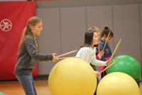 students hitting large exercise balls with drum sticks