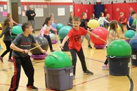 students hit drum sticks against exercise balls next to them