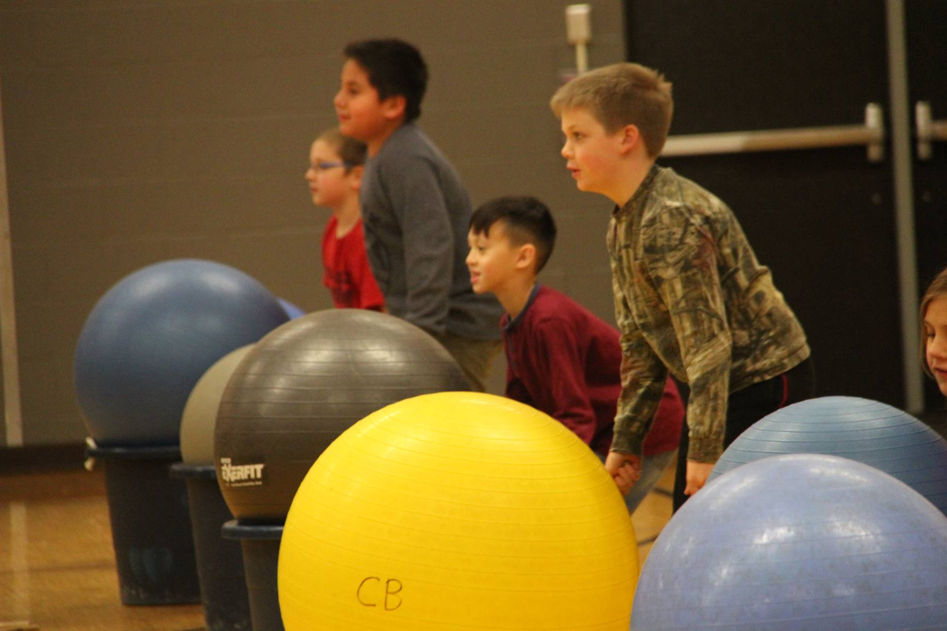 students standing by large exercise balls