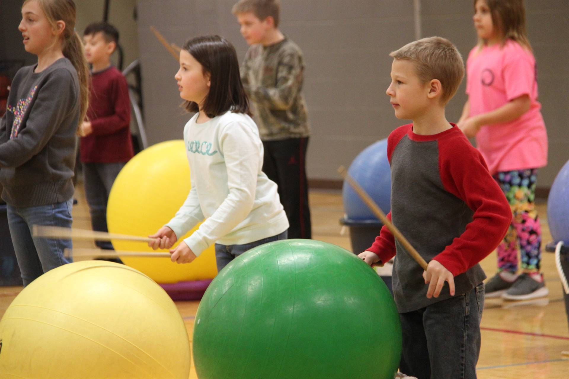 medium shot of students hitting drum sticks on large exercise balls