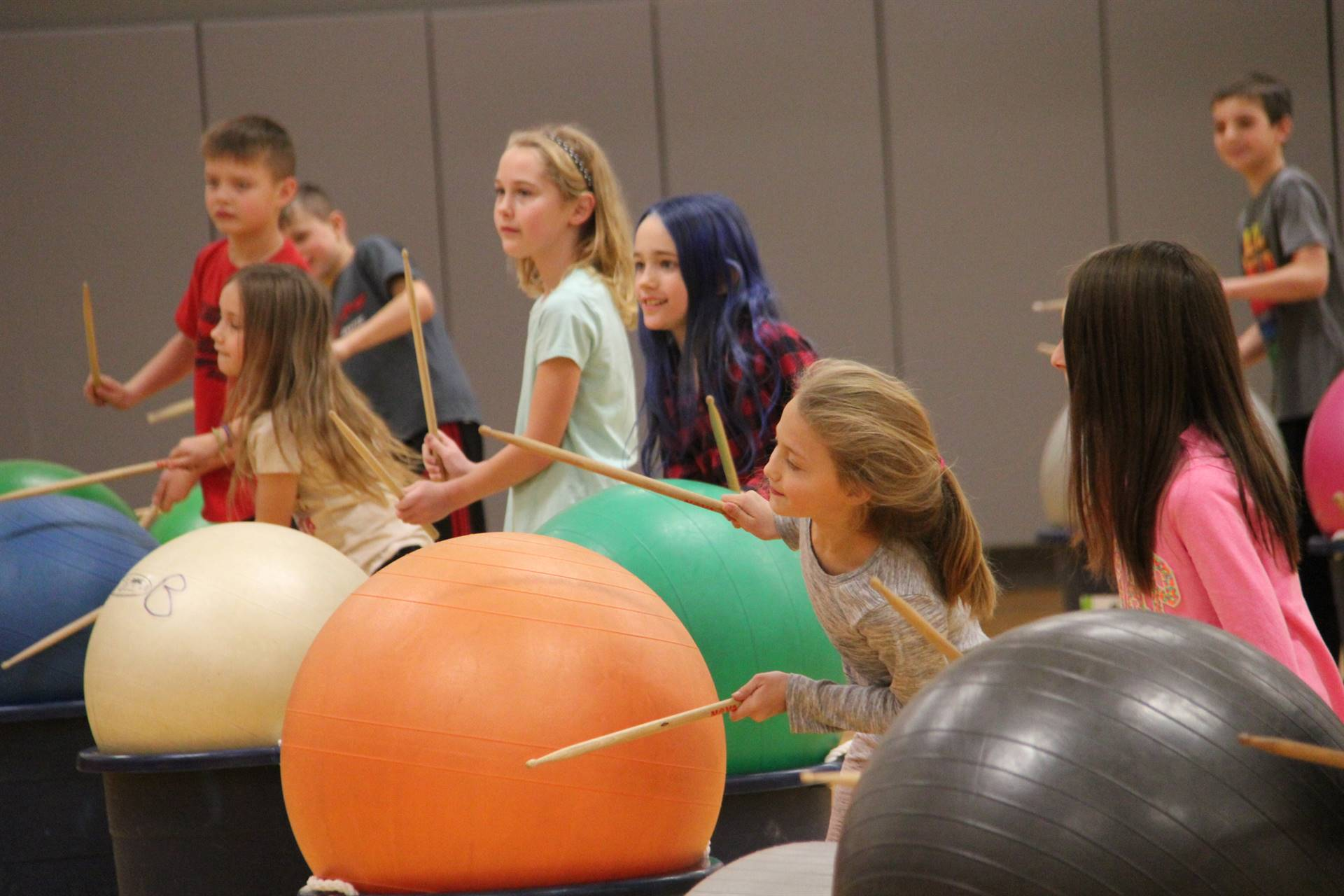 additional students hitting drum sticks on large exercise balls