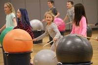 students hitting drum sticks on large exercise balls