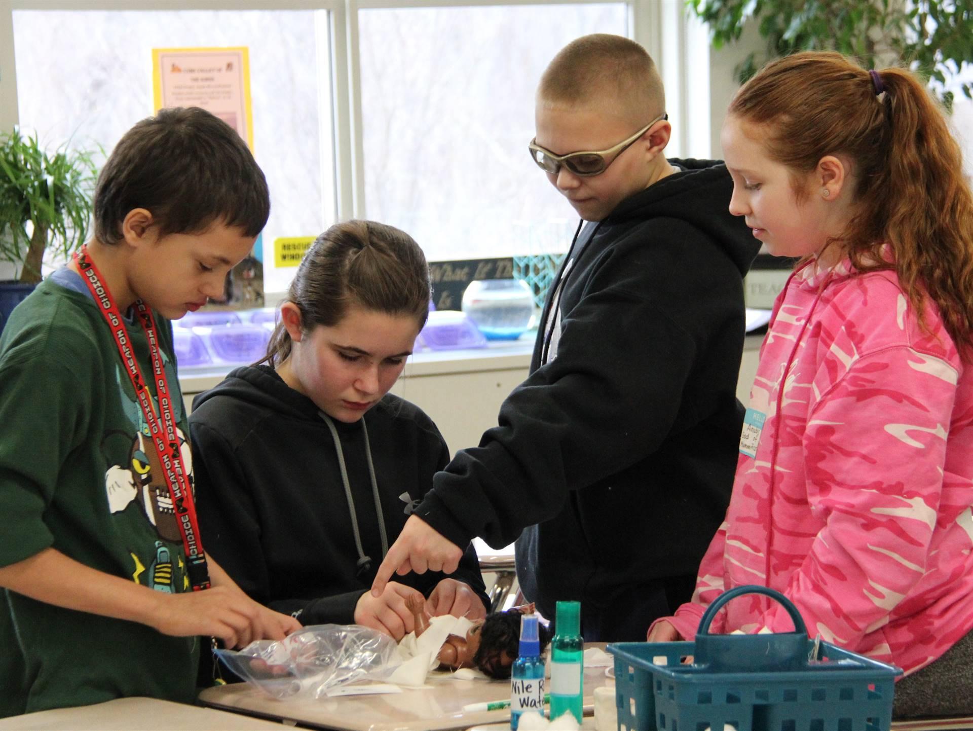 students mummifying doll