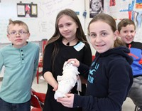 students holding doll they mummified