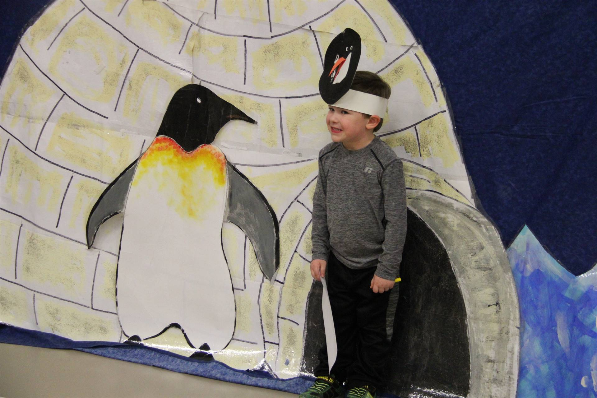 another student standing next to penguin illustration