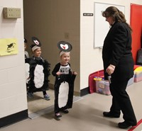 more students entering gym dressed as penguins
