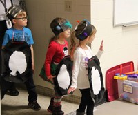 three more students dressed as penguins