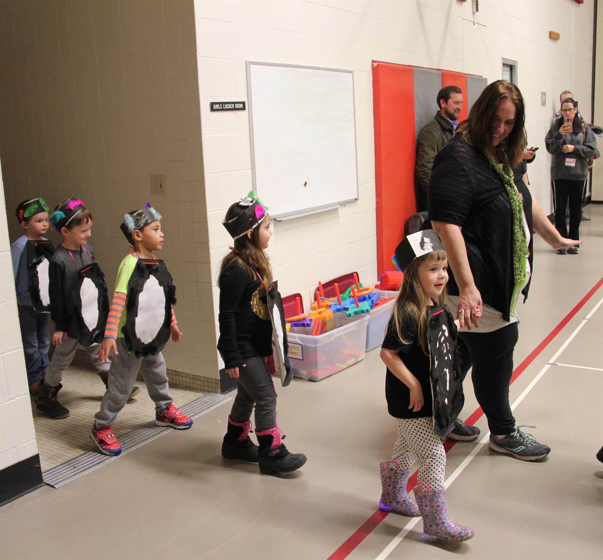 students dressed as penguins entering gym