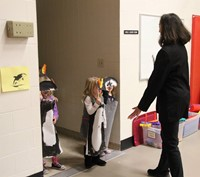 students dressed in penguin costumes entering gym
