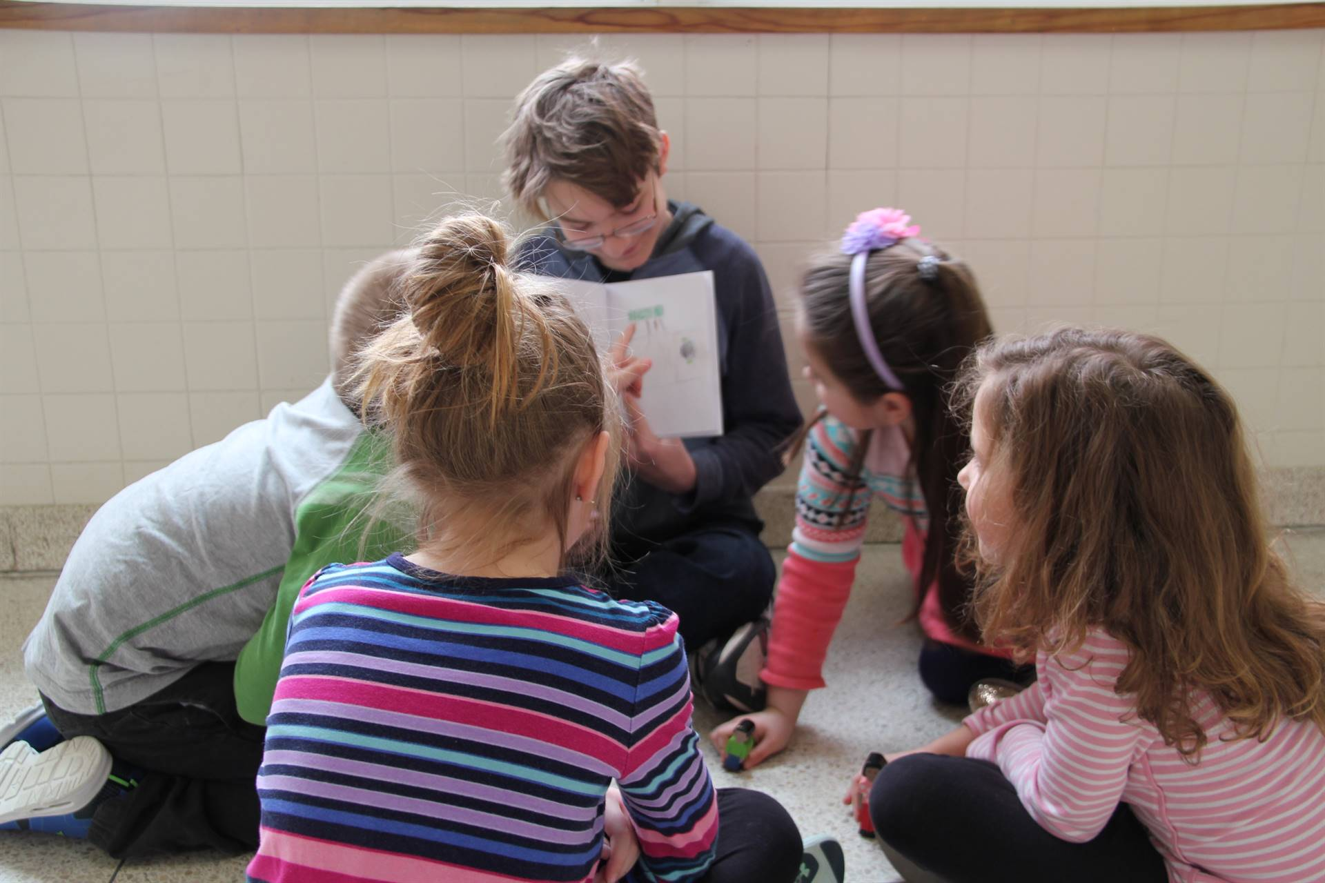 elementary students looking up close to book illustrations