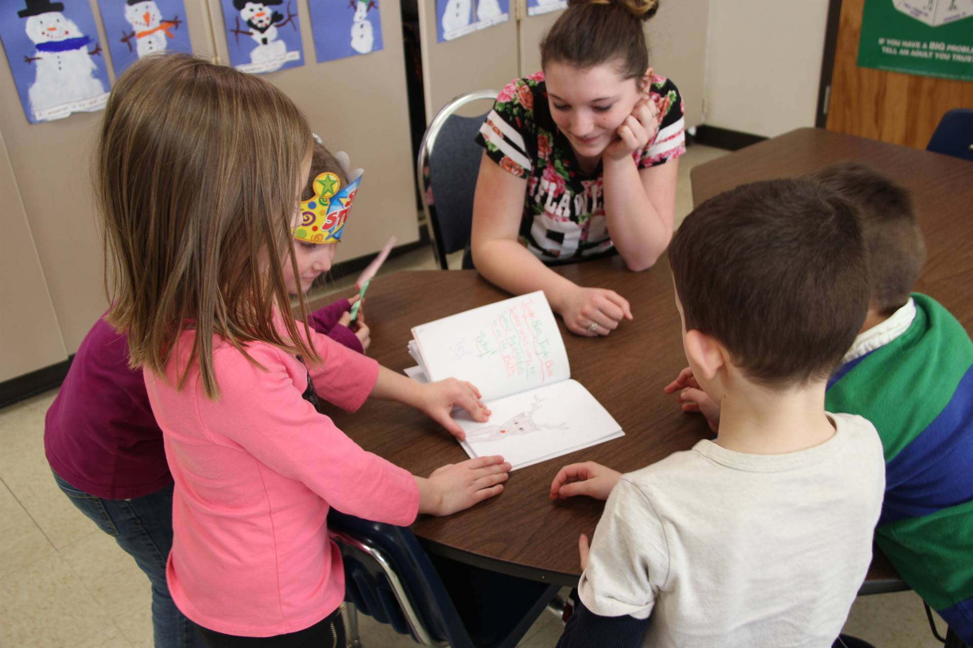 elementary students reading high school students book to her