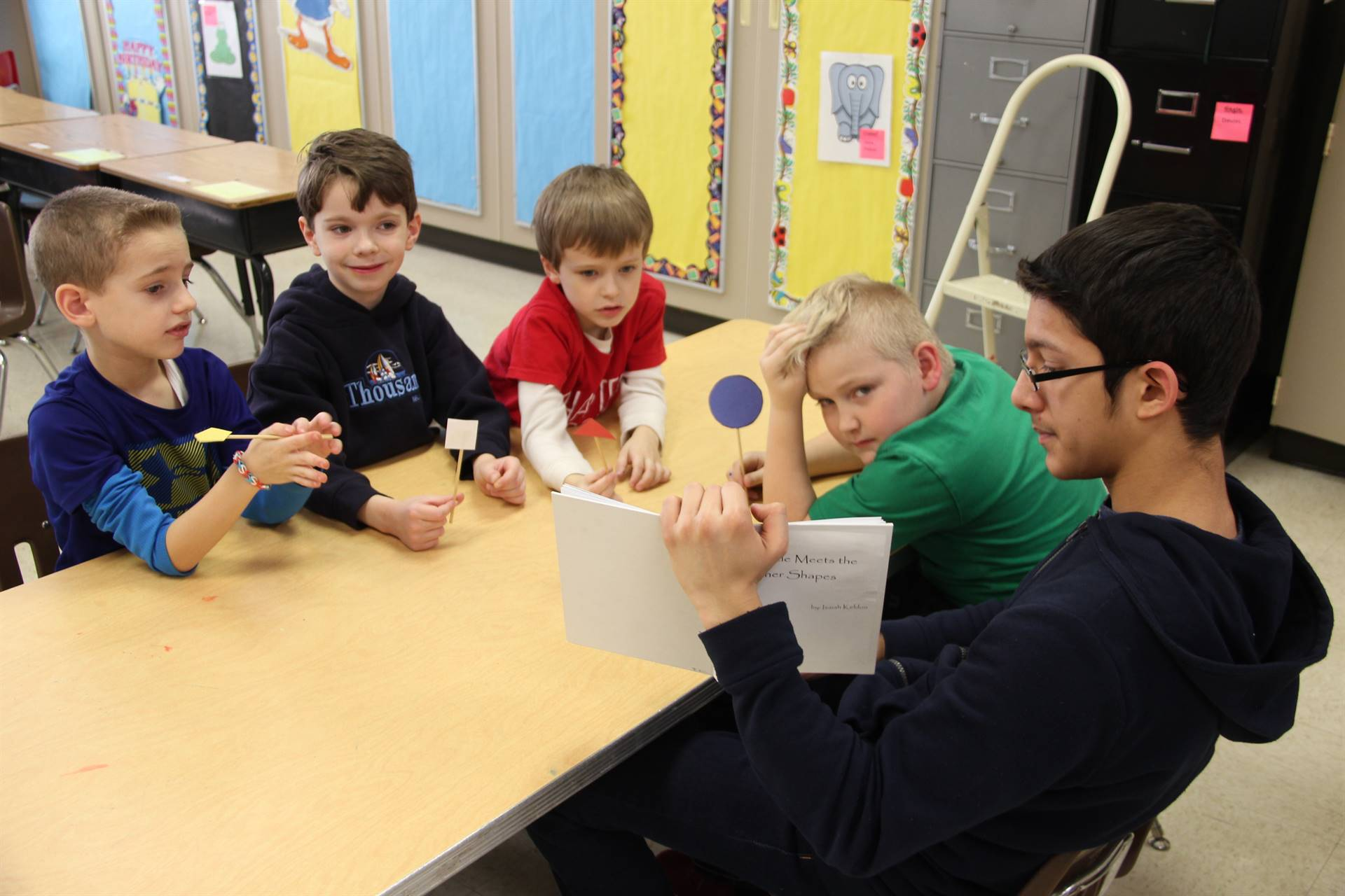 high school student reading book as four elementary students listen