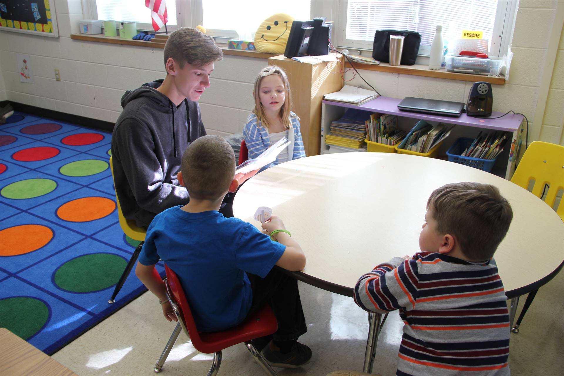 high school student reading book to three elementary students