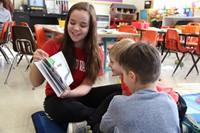 high school student reading book to two elementary students