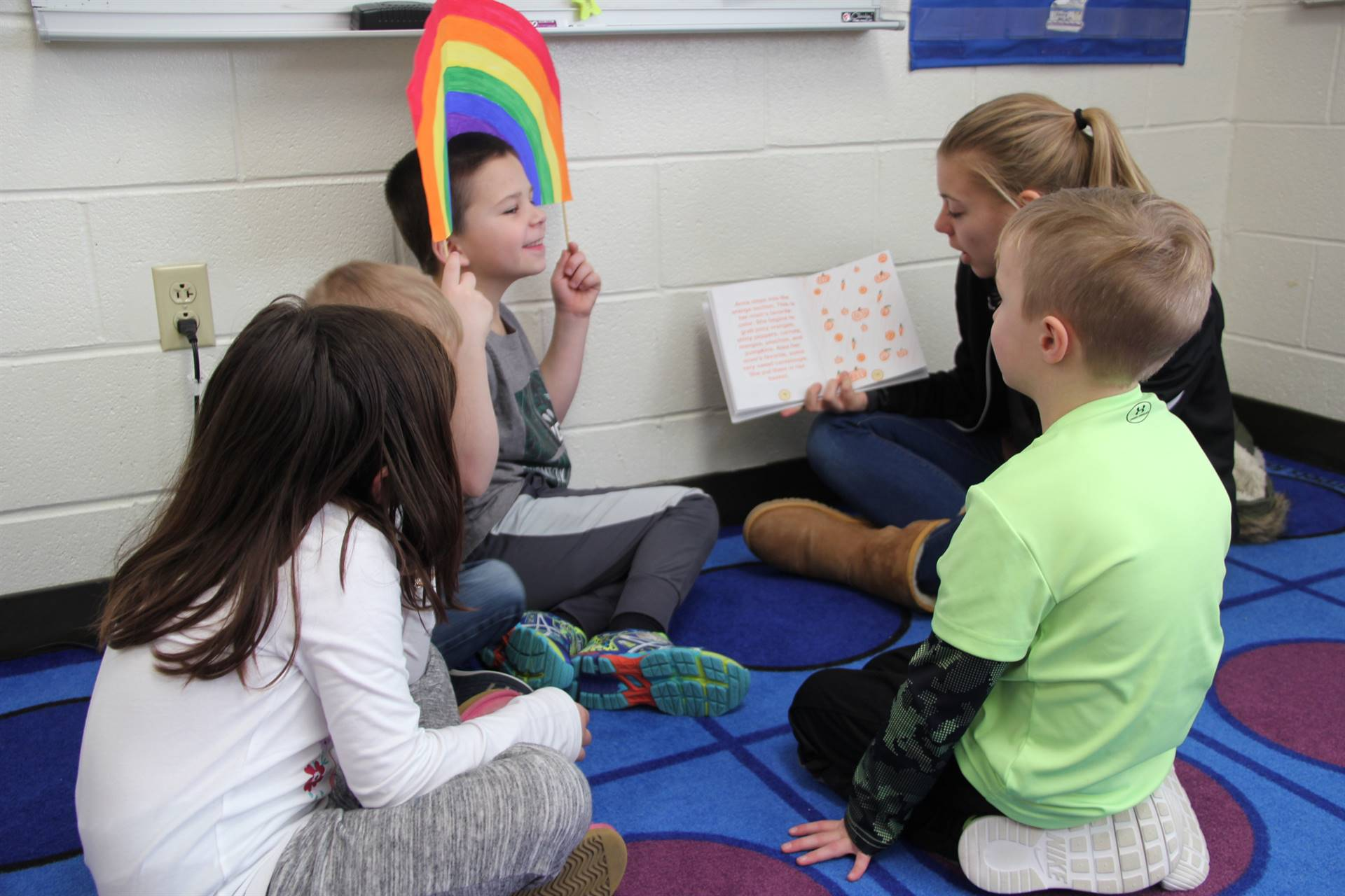high school student reading her story to elementary students