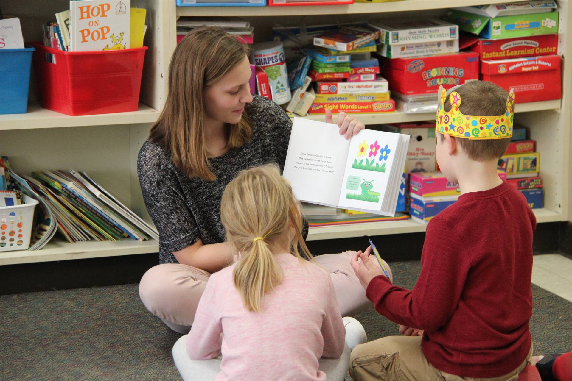 high school student reading her story to two elementary students