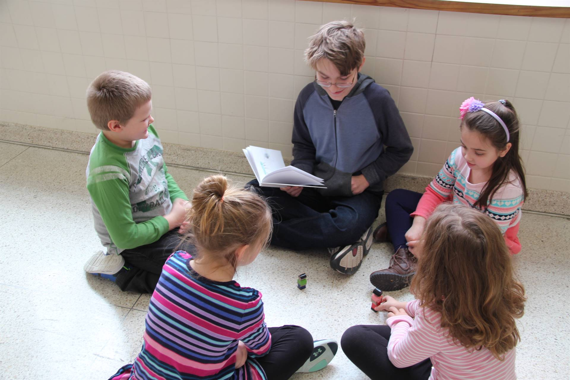 high school student reading his book to four elementary students
