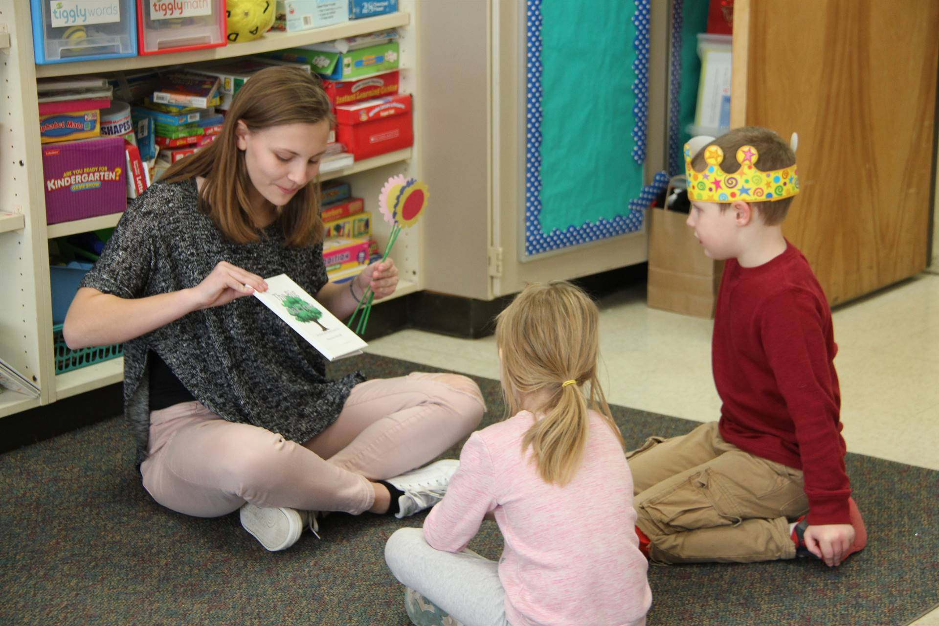 high school student reading story to two elementary students