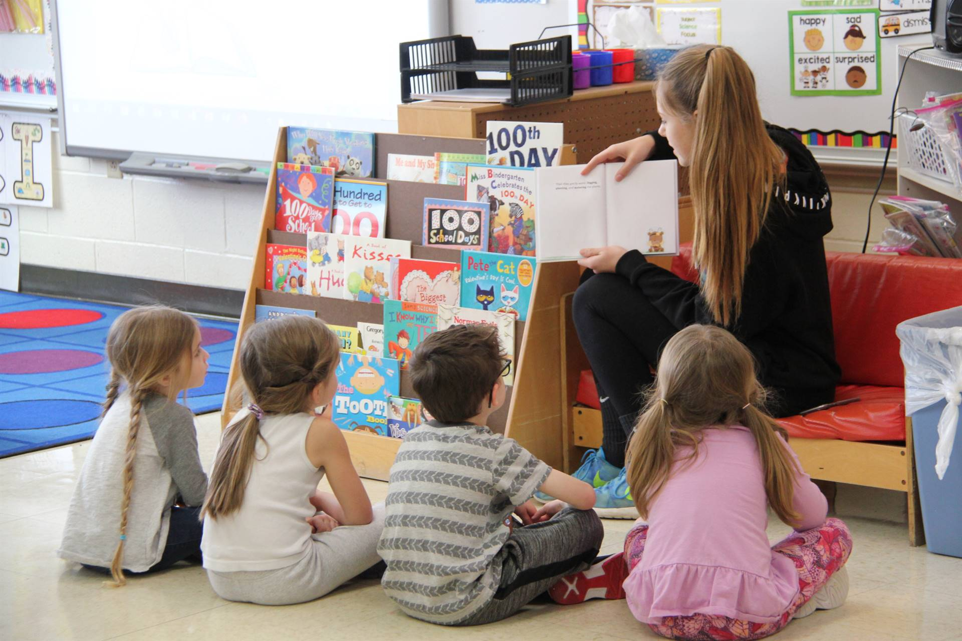high school student reading to elementary students sitting