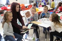 high school student reading to elementary students