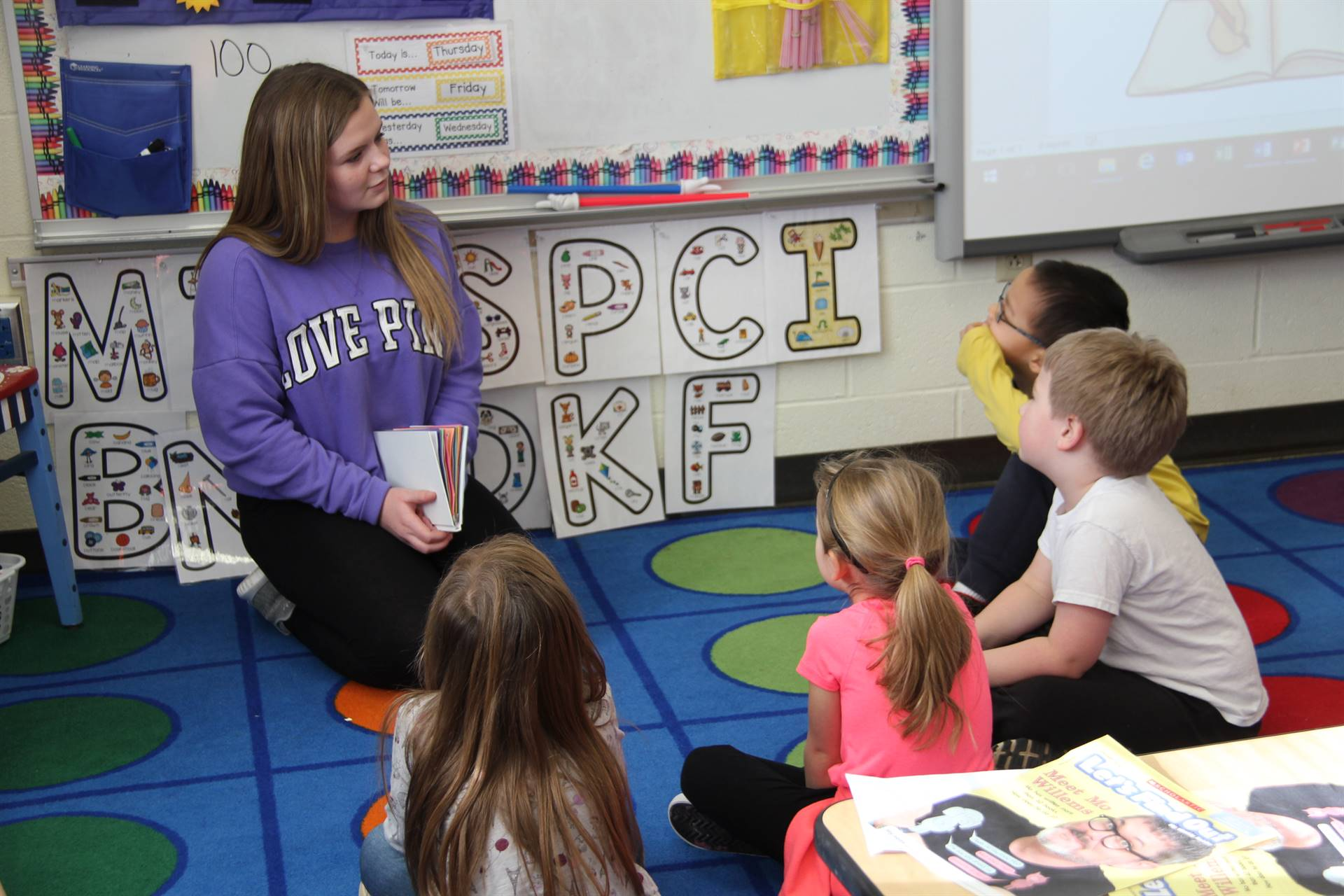 high school student reading to four elementary students