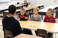 high school student talking to three elementary students