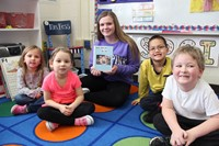 one high school student smiling with book and four elementary students