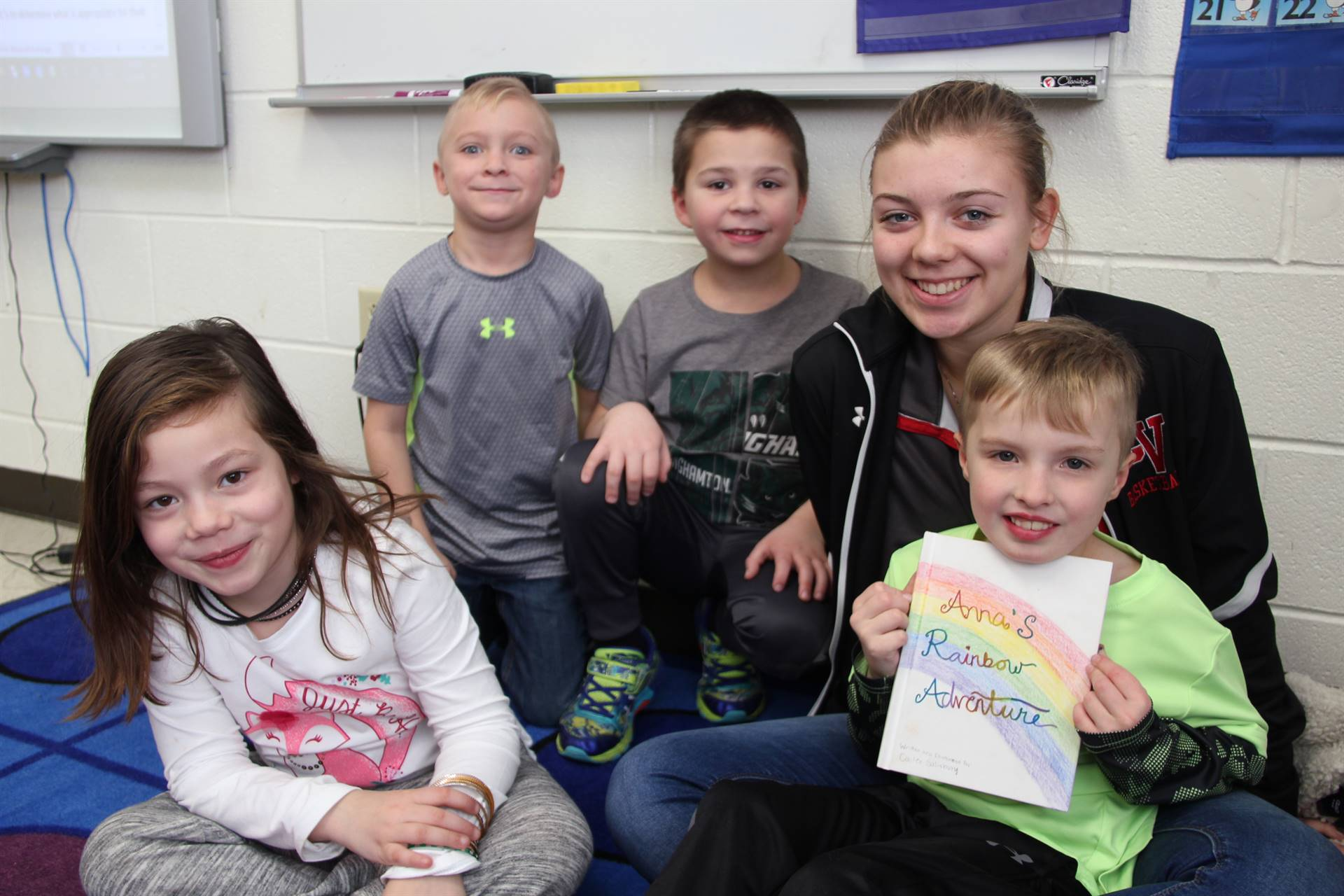 students smiling with book high school student wrote