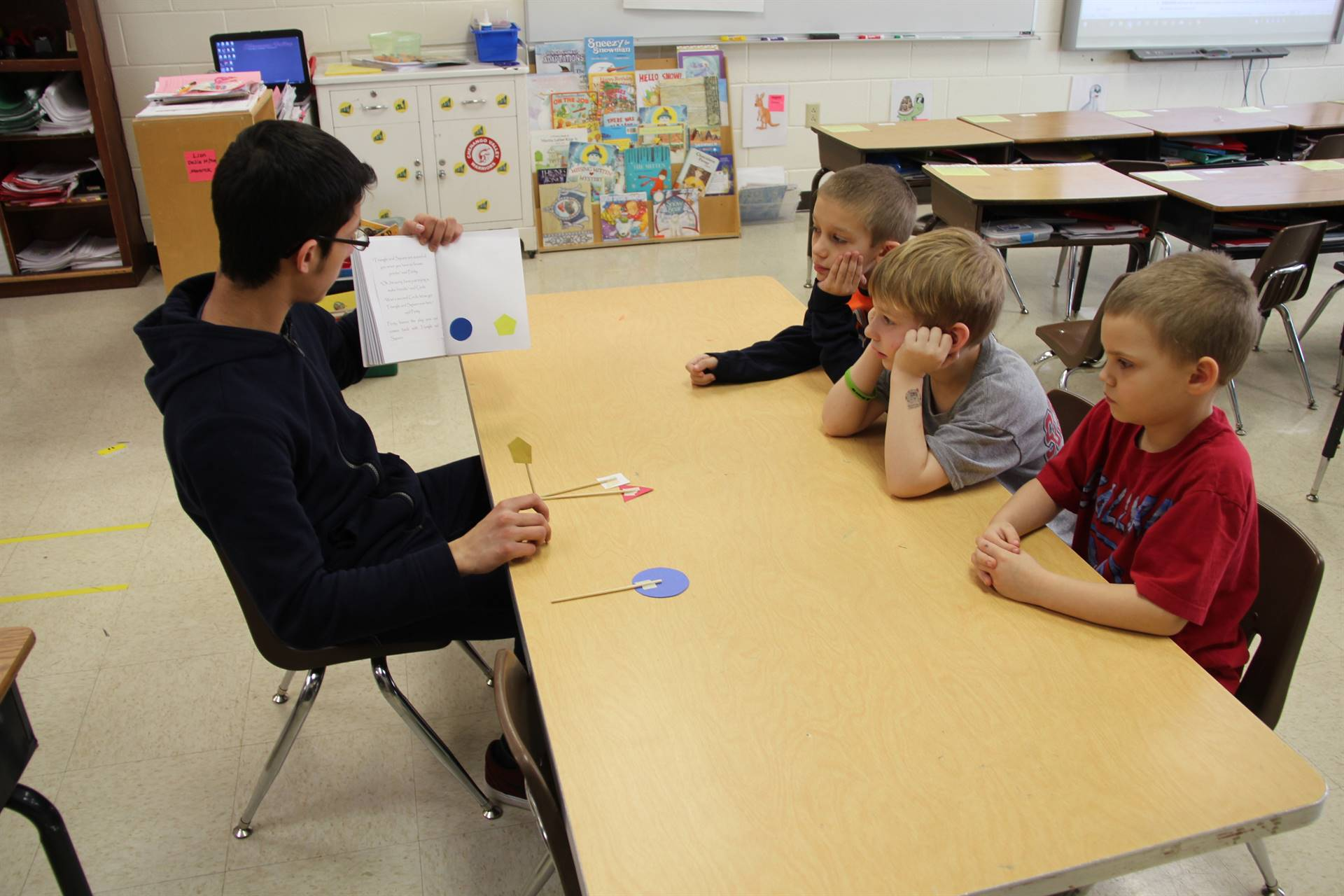 high school student reading to three elementary students