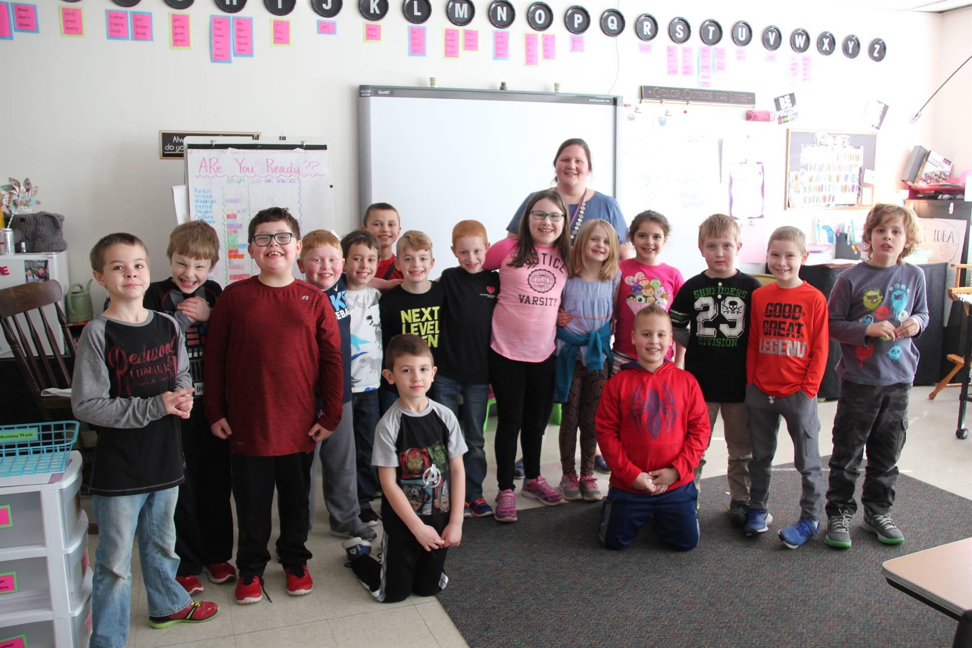 second grade class smiling with teacher