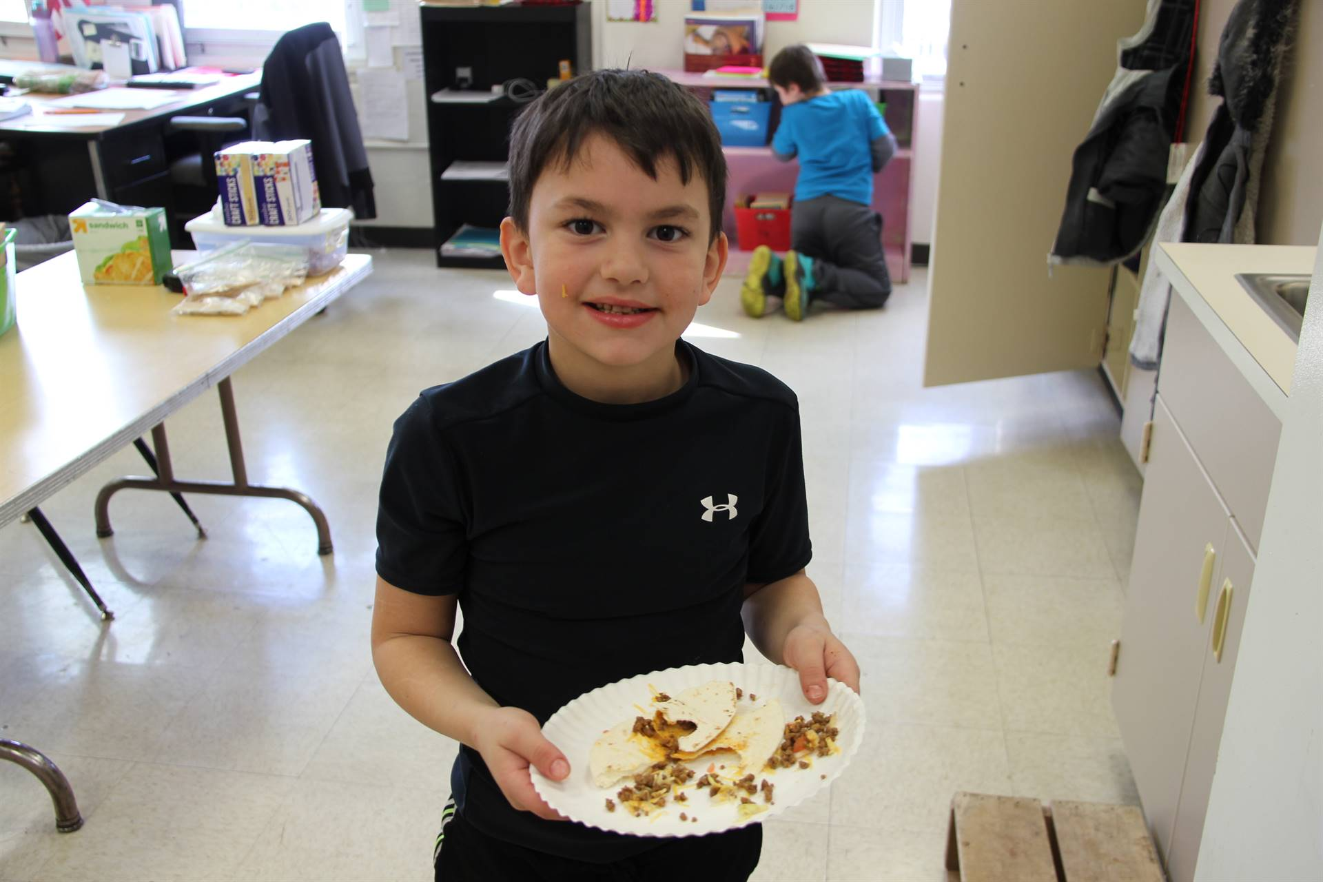 boy holding plate with finished taco