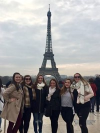 students and teacher in front of eiffel tower