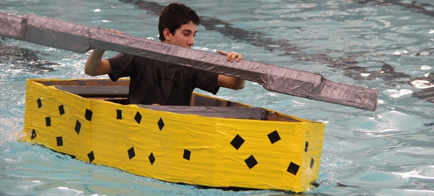 student racing in cardboard boat in pool
