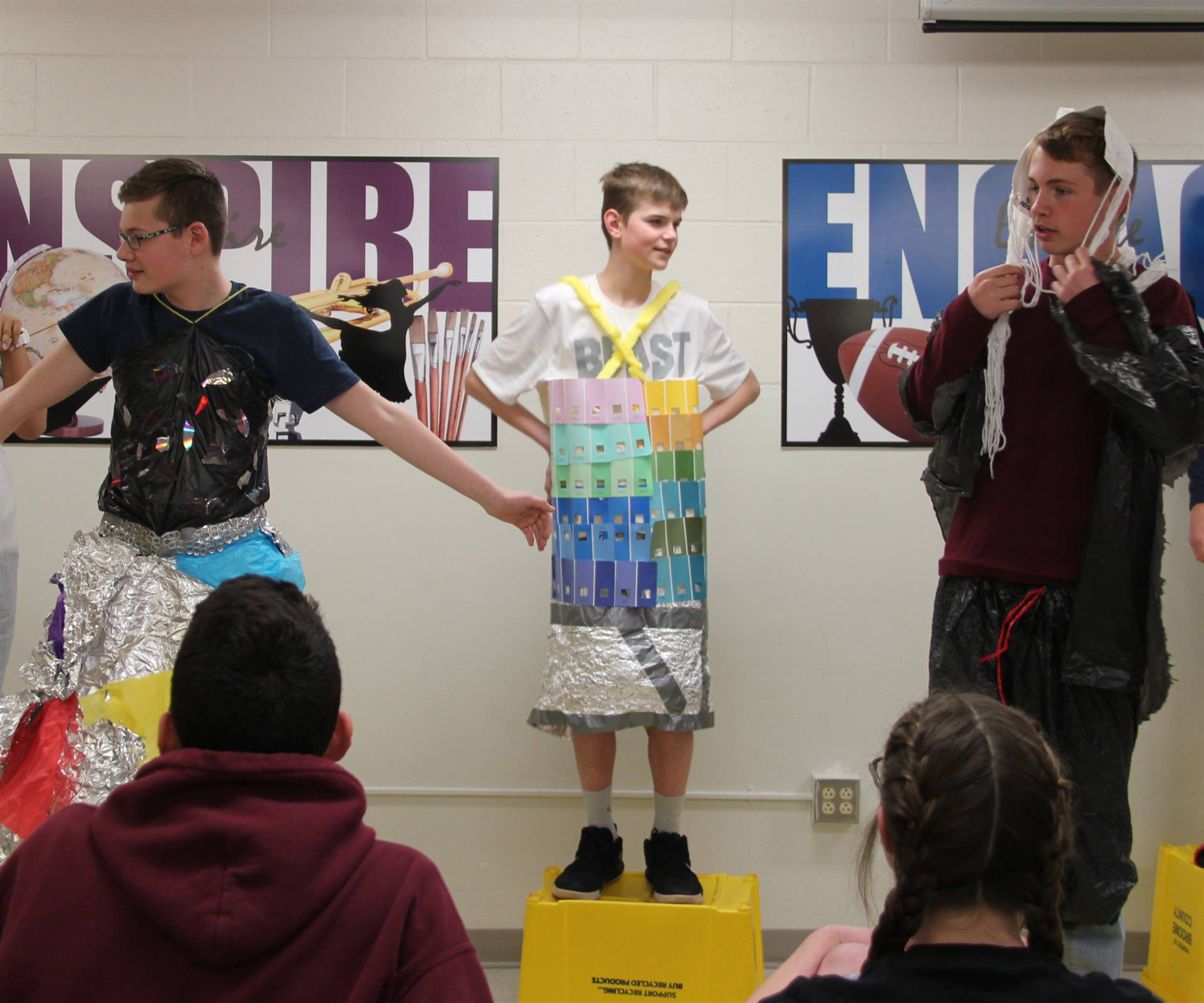 three students dressed in recycled items