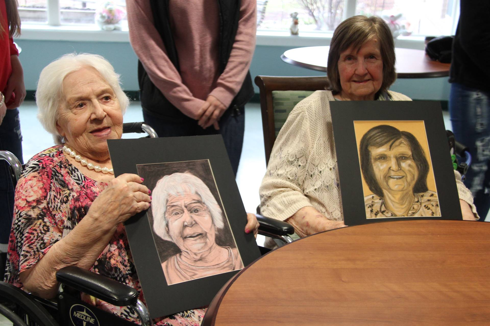 two women smiling holding drawings