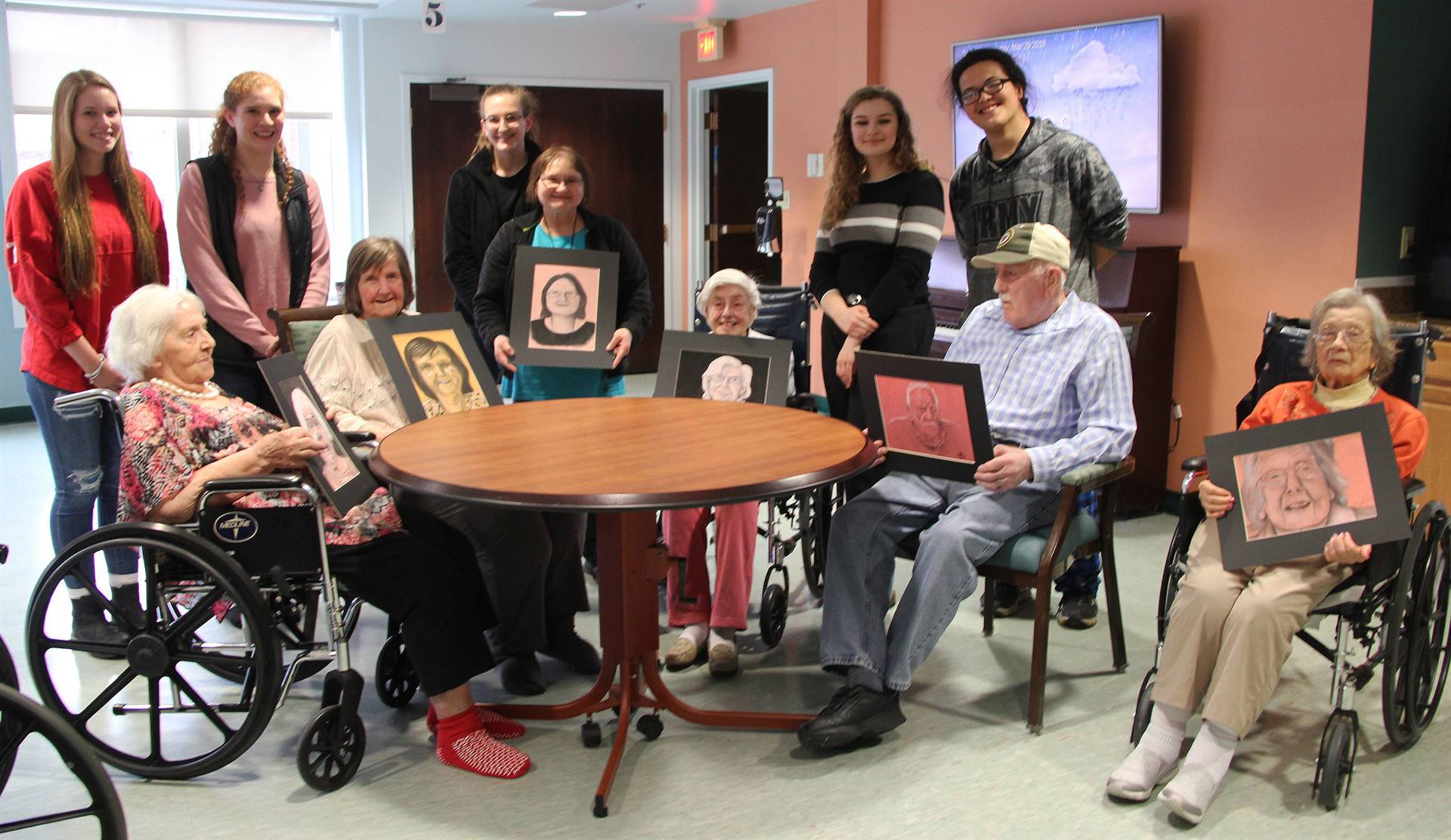 students and residents with drawings at table