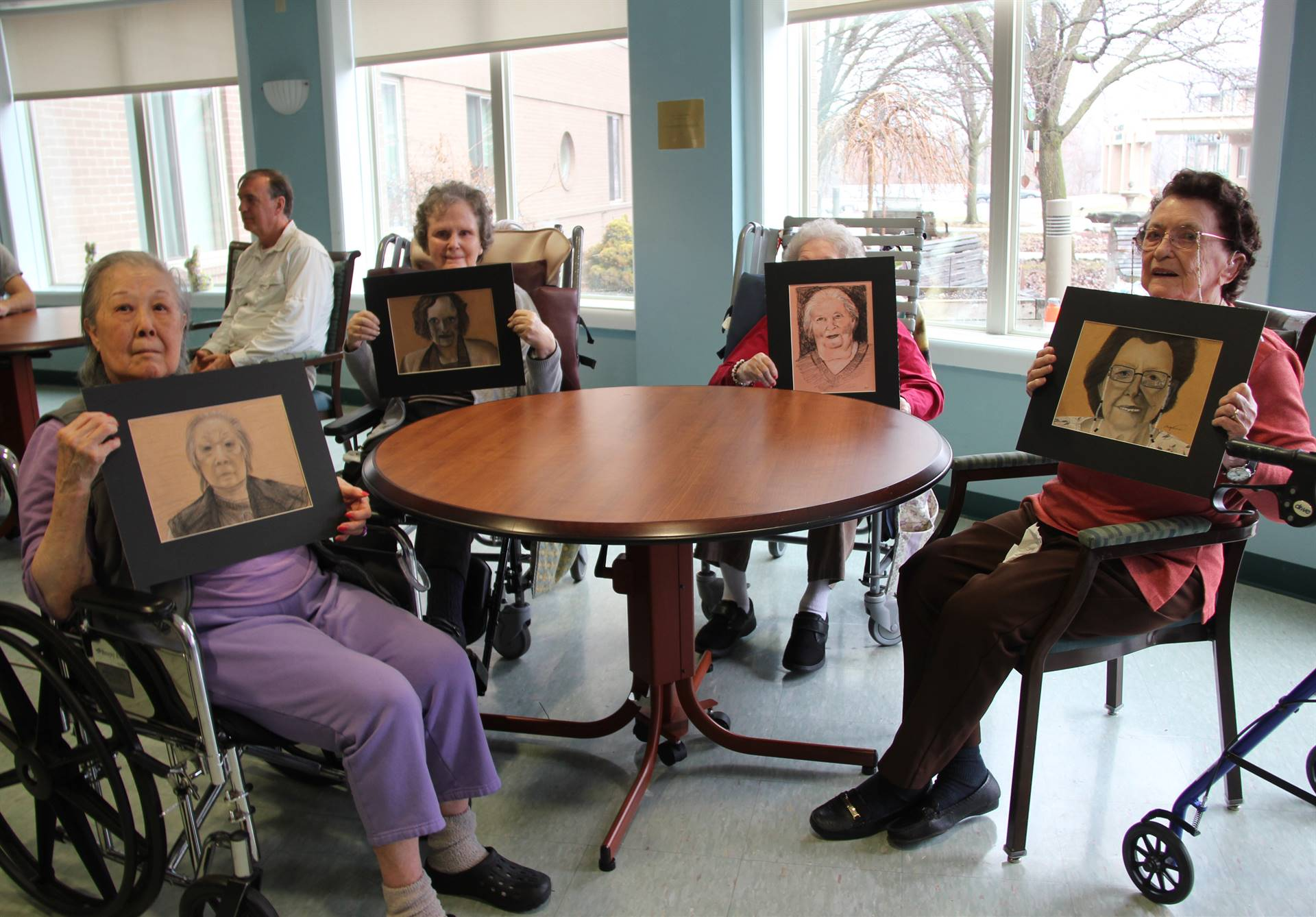 four residents holding drawings of them