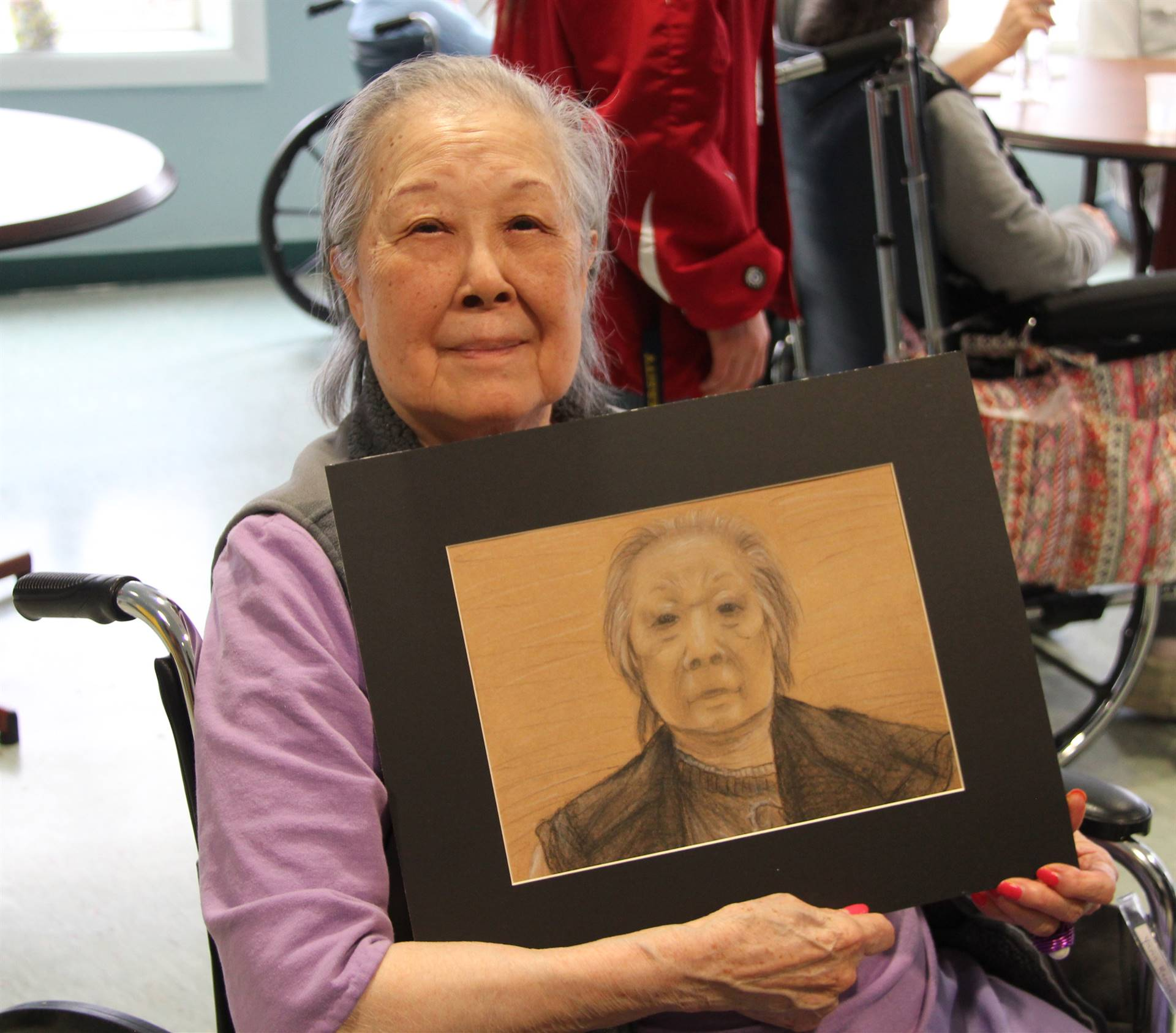 woman smiling holding picture of herself