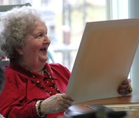 woman smiling while looking at drawing