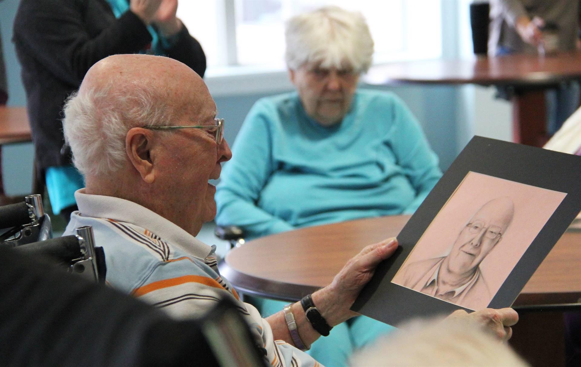 man looking at drawing of himself