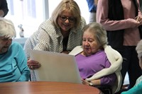 nursing home employee and resident looking at drawing