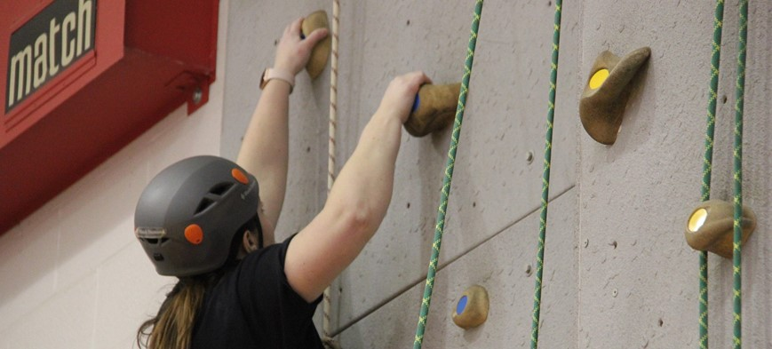 staff member climbing rock wall