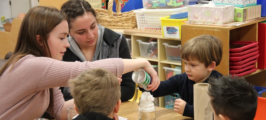 high school students working with pre k students on science projects