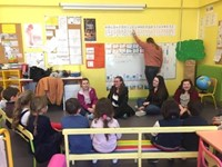 high school students talking about the alphabet with elementary students