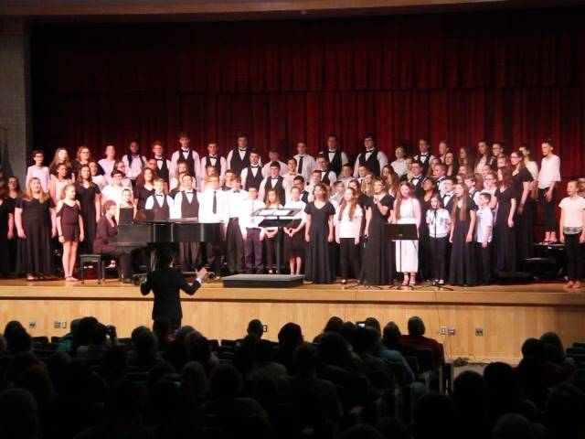 medium shot of high school and middle school choirs singing together