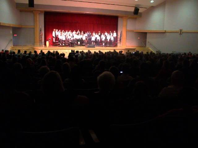 wide shot of auditorium with chorus singing