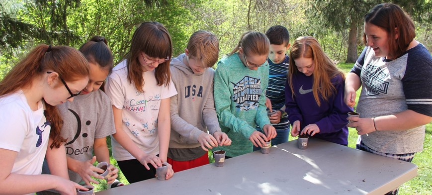 students planting seeds in cup