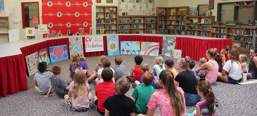 wide shot of students watching puppet show