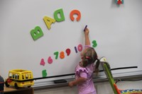 student playing with magnet letter