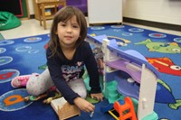 student playing with toy house